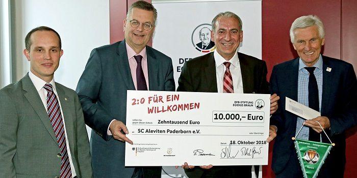 F1_Scheckübergabe an Verani Kartum (2vr) mit Reinhard Grindel Eugen Gehlenborg (r) und Tobias Wrzesinski (l)